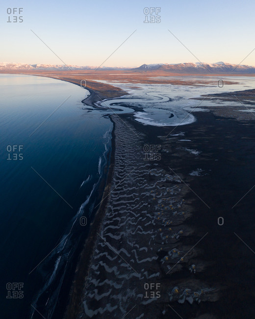 Aerial view of a unnamed river meandering through a black sand shore in North East Iceland, Thingeyrar.