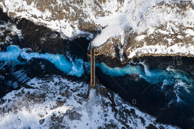 Aerial view of bridge over Bruarfoss waterfall with cascading blue water flowing through winter landscape in South Iceland.