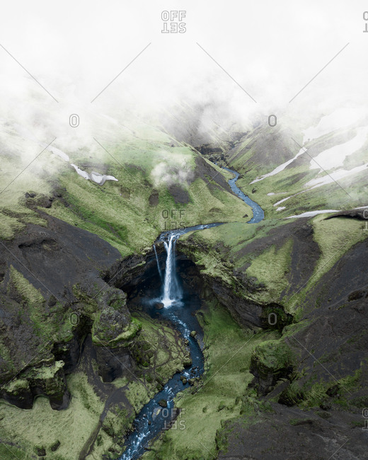 Aerial view of Kvernufoss waterfall seen from above the clouds in green valley in South Iceland.