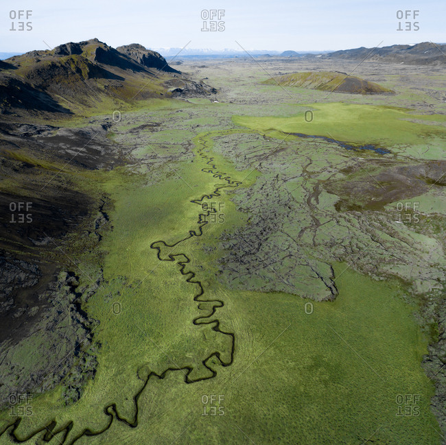Aerial view of a twisted river flowing through green lava fields and mountains, close to Djupavatn in Reykjanes Peninsula, Iceland.