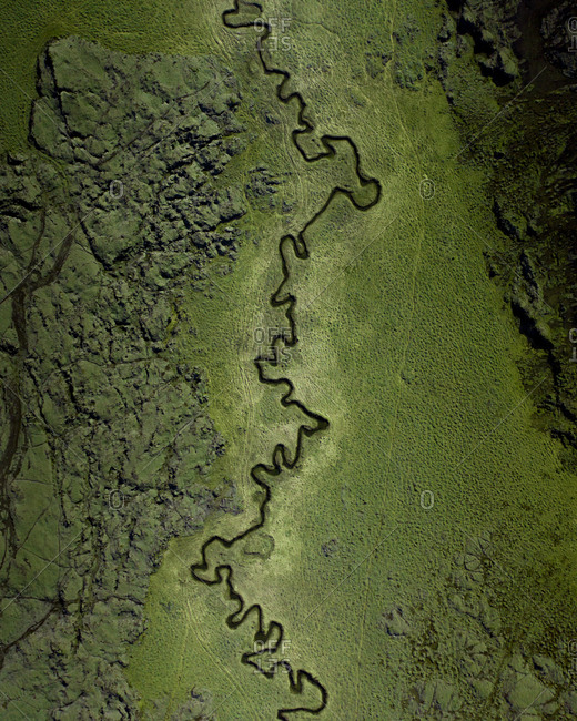 Aerial view of a twisted river flowing through green lava fields, close to Djupavatn in Reykjanes Peninsula, Iceland.