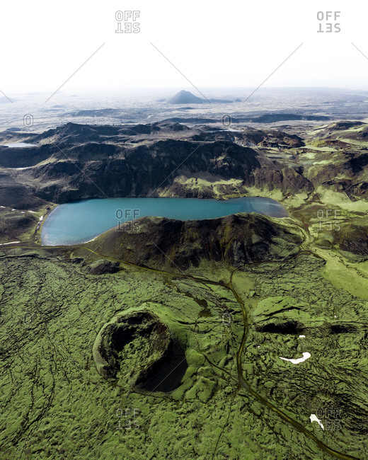 Aerial view of lake Djupavatn and Keilir mountain in the distance, surrounded by green lava fields and an old volcanic crater Reykjanes Peninsula, Iceland.