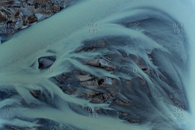 Aerial view of beautiful abstract blue patterns in the water of glacial river in North Iceland.