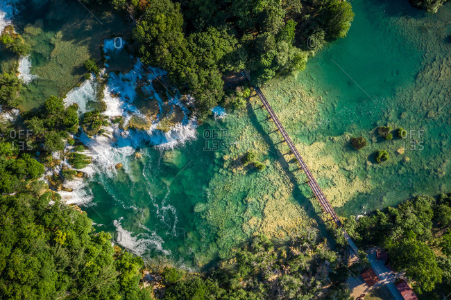 Aerial view of Skradinski Buk waterfall surrounded by trees with turquoise water in Lozovac, Croatia