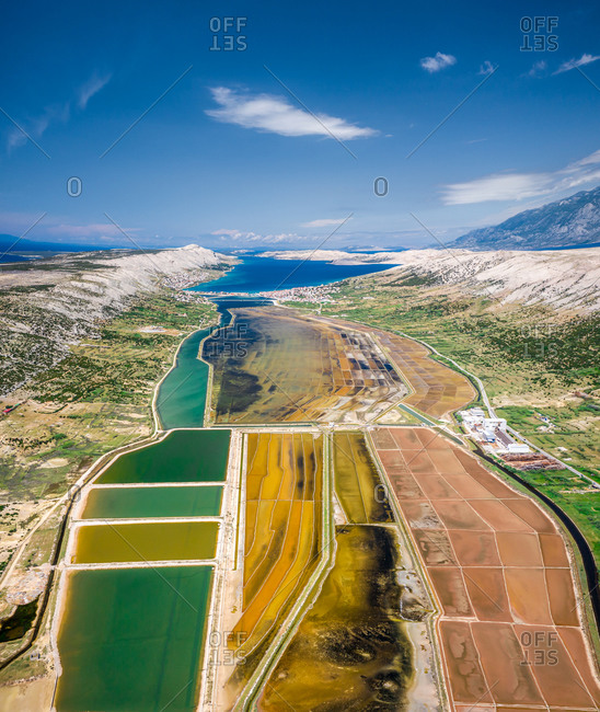Aerial view of salt extraction lakes on the shoreline in Opcina pag, Croatia