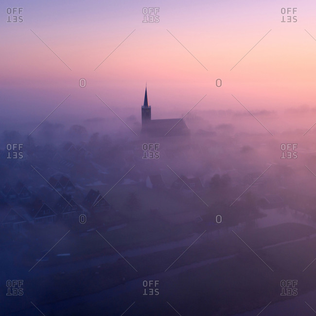 Aerial view of  the village of Schermerhorn in the mist, with it's church, houses, canals en farmer's land, municipality of Alkmaar, North Holland, Netherlands