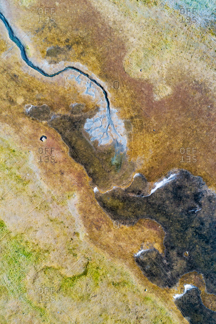 Abstract aerial view of a small dried up stream in stony grassland near the coastline, Westfjords, Iceland