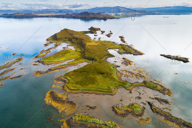 Aerial view of amazingly shaped island in a fjord with reflection of the sky, Berufjordur, Westfjords, Iceland