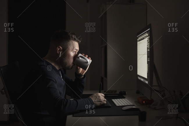 Man with earbuds drinking coffee and working late at computer in dark room