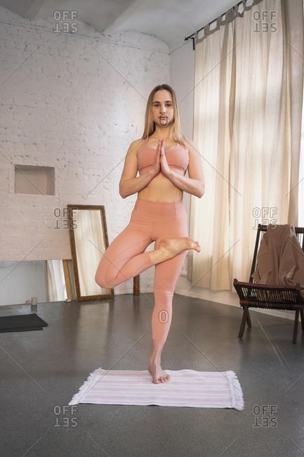 Portrait confident young woman practicing yoga tree pose in yoga studio