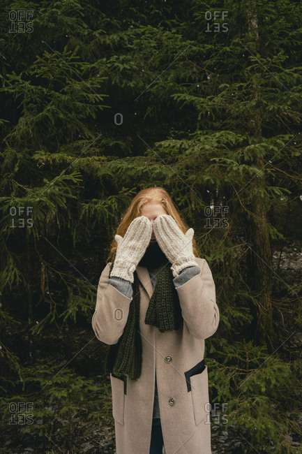 Portrait playful woman with mittens covering face in woods