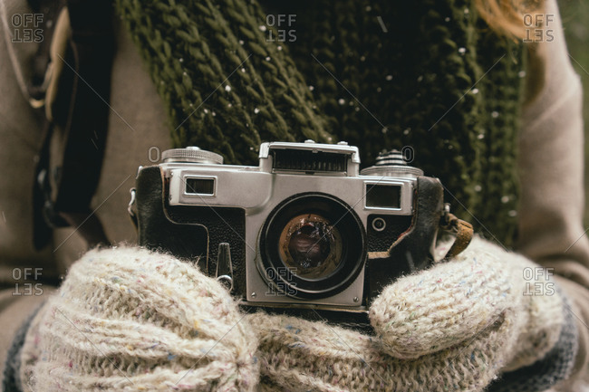 Close up woman in mittens holding retro camera