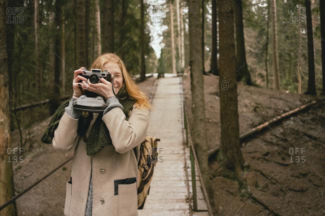 Portrait woman using retro camera on footbridge in woods