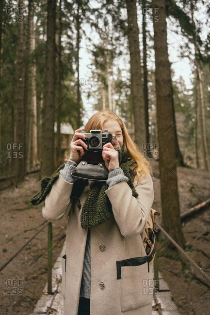 Portrait woman using retro camera in woods