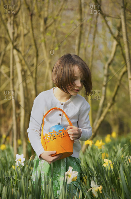 Girl with Easter egg basket in field of daffodils