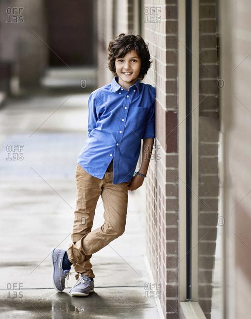 Portrait confident boy leaning against wall