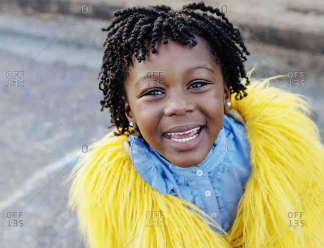 Portrait happy girl in yellow furry jacket
