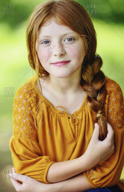 Portrait beautiful girl with braided red hair and freckles