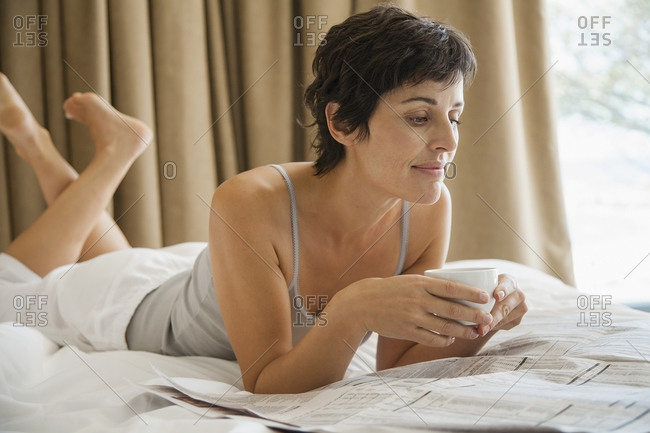 Woman relaxing on bed reading newspaper with coffee