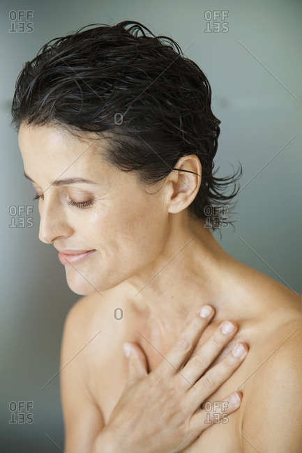 Serene beautiful woman with wet hair and bare chest