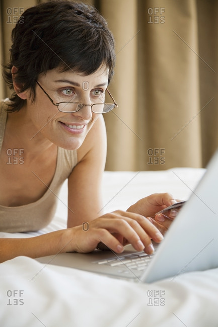 Woman online shopping with credit card and laptop on bed