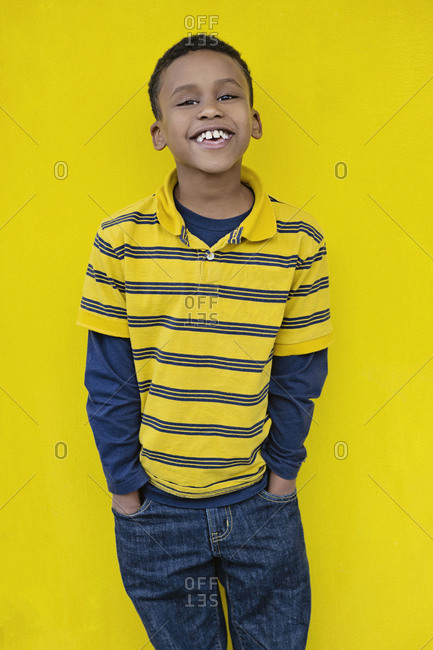 Portrait confident boy against yellow background