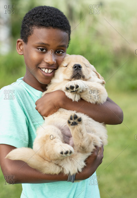 Portrait happy boy holding Golden Retriever puppy