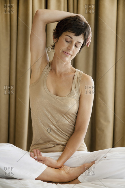 Serene woman stretching while sitting