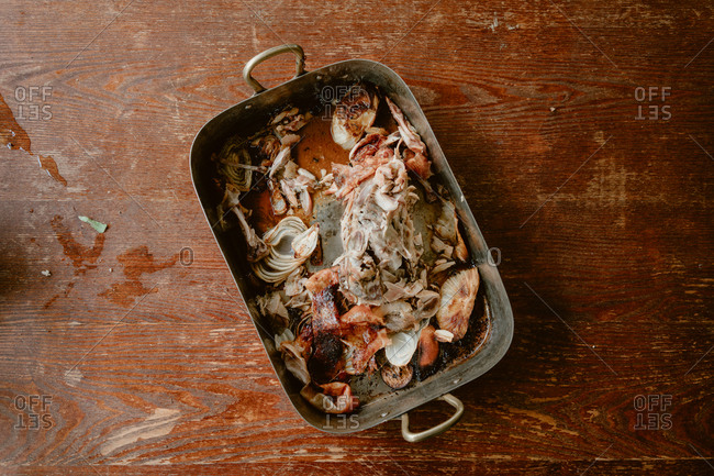 Leftover chicken bits in a roasting pan on a wooden table
