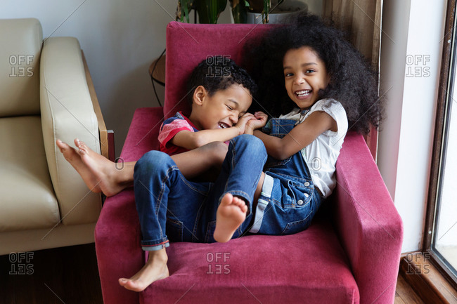 Young boy and girl tickling each other on chair
