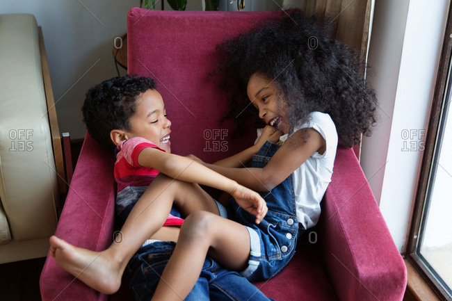 Brother and sister tickling each other on chair