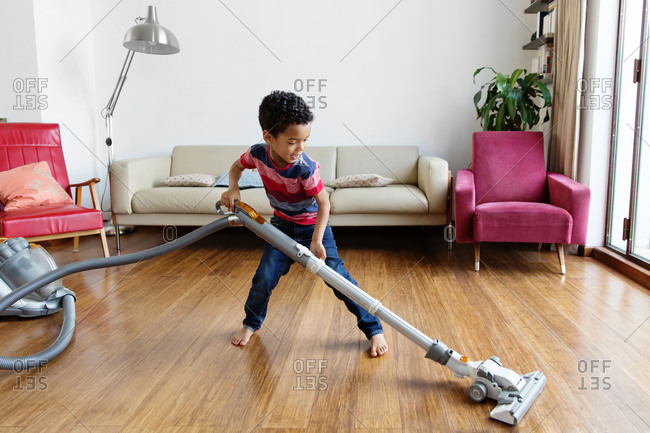 Young boy using vacuum on hardwood floor at home