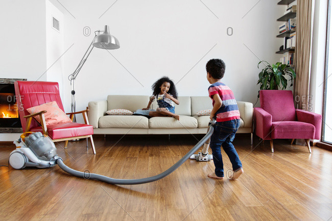 Young boy using vacuum at home while sister watches him