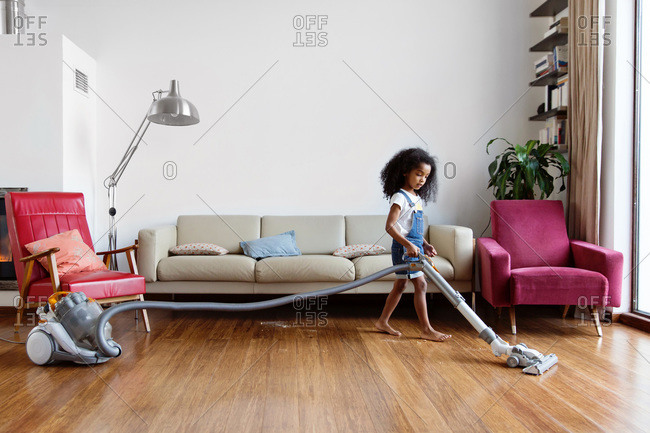 Young girl using vacuum on hardwood floor at home