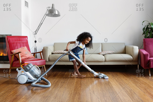 Smiling young girl using vacuum on hardwood floor at home
