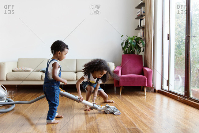 Young girl helping little brother use vacuum at home