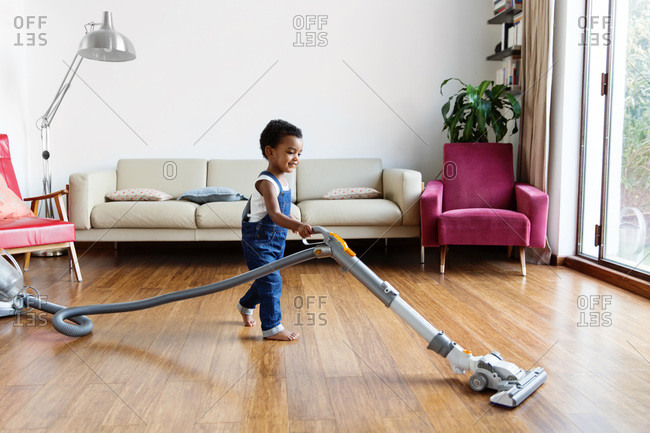 Smiling toddler using vacuum on hardwood floor at home
