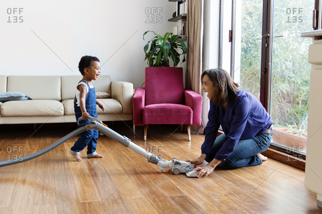 Happy mother helping smiling boy use the vacuum at home