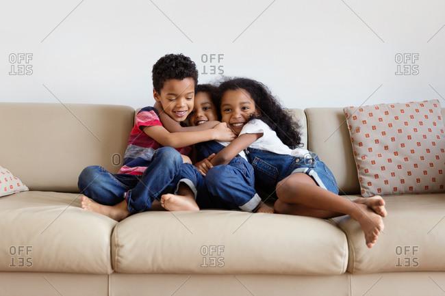 Smiling siblings cuddling on sofa