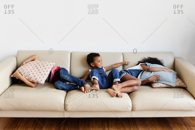 Funny children playing hide and seek on sofa