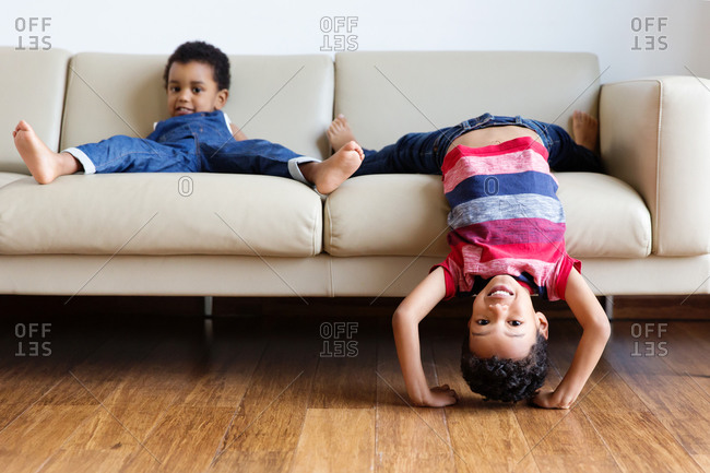 Funny young boys being silly on sofa