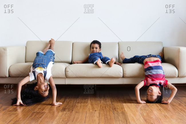 Playful young children being silly on sofa