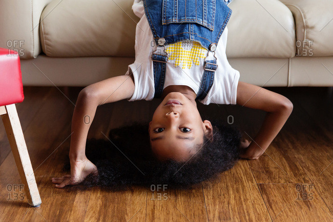 Portrait of young girl upside down doing headstand in living room