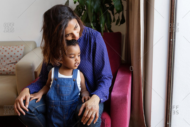 Tender moment between mother and toddler boy in living room