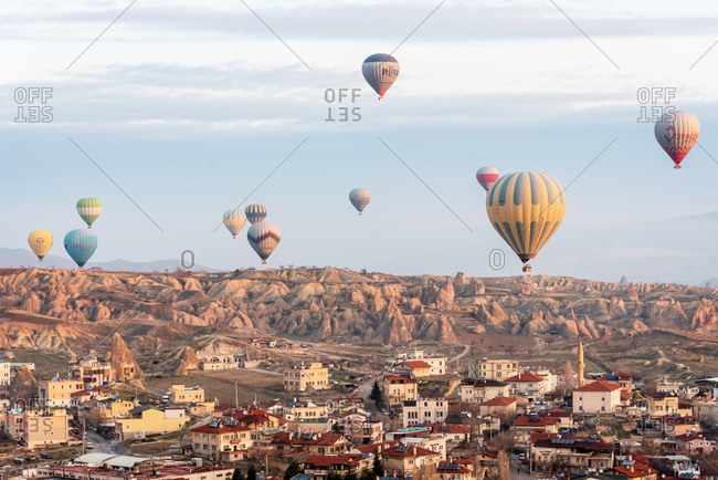 February 26, 2018: Lots of colorful air balloons flying over valley and mountains. Goreme, Cappadocia, Turkey.