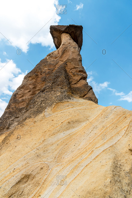 From below big natural post with rock on top in Fairy Chimneys, Cappadocia, Turkey.