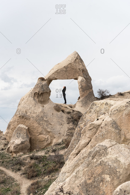 Side view of woman leaning and relaxing at rock in Cappadocia, Turkey.