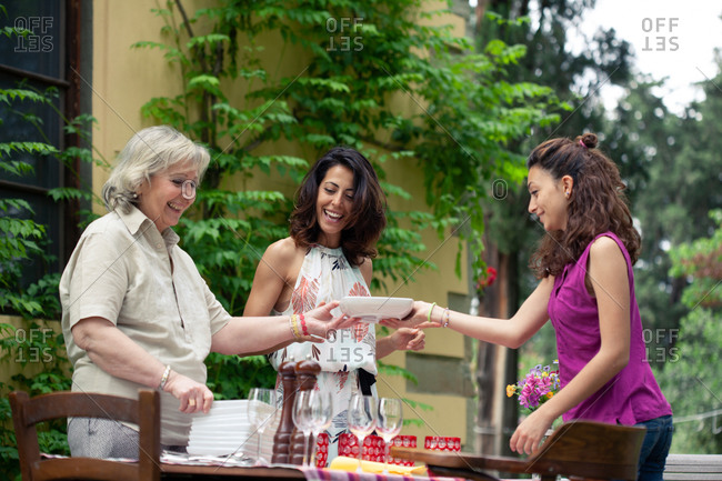 Three generations of female family preparing table for outdoor meal