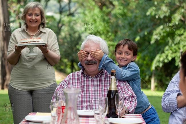 Senior man being surprised with birthday cake
