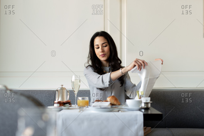 Young woman preparing napkin while having champagne breakfast atboutique hotel in Italy